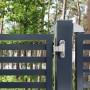 Detail anthracite gate in front of forest bonheiden