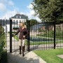 Equestrian leaving black ornamental gate at villa / Equestrian leaving black ornamental gate at villa