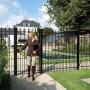 Equestrian leaving black ornamental gate at villa