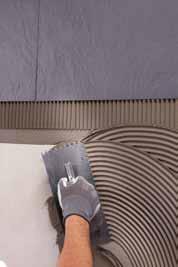 Intinderea uniforma a adezivului ULTRALITE S1 cu spatula dintata nr 6 pe perete si aplicarea acestuia
