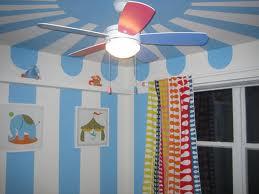 Tema circului, redata simplu cu ajutorul dungilor albe si albastre (foto Pottery Barn Kids) - Pictura murala, autocolantele sau accesoriile suspendate de tavan creeaza o atmosfera specifica varstei