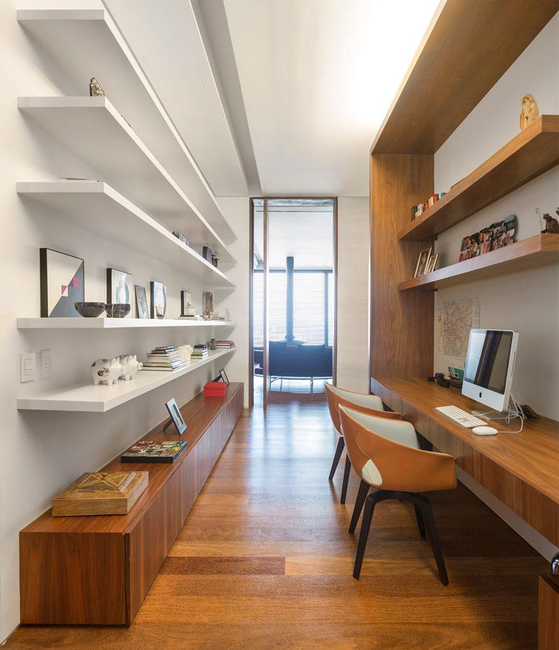 10. Iata un birou amenajat intr-un spatiu ingust. Predomina rafturile lungi pe o parte si biroul pe cealalta.