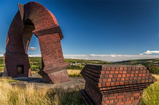 """<b>2. Cosul de fum rasucit Simnai Dirdro</b> <p style=""""text-align: left;"""">Un cos fum impunator, care se rasuceste opt metri in aer, """"Simnai Dirdro"""" (""""Cosul de fum rasucit""""), se afla la nord de Valea Rhymney din Tara Galilor de Sud. A fost proiectat de artistul Brian Tolle din New York, fiind prima lui instalatie in Marea Britanie. Sculptura lunga de 16 metri a fost dezvaluita in 2010 si reprezinta o interpretare moderna a clasicului cos de fum.   A fost acoperita cu o substanta speciala pentru durabilitate si rezistenta si pictata manual de artisti de la un teatru din Marea Britanie, fiind ridicata in pozitie verticala cu macaraua.</p>"""