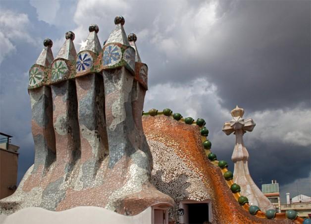 """<b>4. Cosurile de fum ale edificiului Casa Batllo</b> <p style=""""text-align: left;"""">Cladire restaurata de acelasi Antoni Gaudi, Casa Batllo a fost prevazuta cu mai multe  de cosuri de fum colorate. Fiecare parte a edificiului cunoscut si sub numele de """"Casa oaselor"""", arata, ca in cazul oricarei alte creatii a lui Gaudi, diferit. Cladirea se remarca prin lipsa liniilor drepte si prin utilizarea placilor ceramice colorate, incorporate in fiecare zona a casei. Chiar si cosurile de fum sunt acoperite complet cu placi ceramice pline de culoare.</p>"""