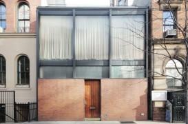 O casa din caramida si sticla ingramadita intre alte doua imobile