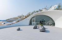 Un muzeu ascuns în dunele de nisip Ascunsa aproape complet de nisip, anvelopanta din beton a constructiei a fost realizata in mare masura manual de catre localnici, iar arhitectii au decis sa