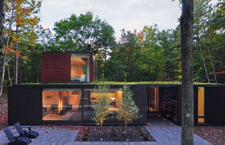 O casa cu acoperisuri verzi se ascunde de minune in padure
