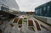 """Un acoperis verde intre doua cladiri de birouri mascheaza spatiile unei gradinite Fasii unduitoare de verdeata reusesc sa camufleze volumul unei gradinite inserat intre doua imobile de birouri. Constructia reprezinta dorinta arhitectilor de a crea """"un peisaj locuibil""""."""