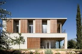 O casă cu vedere spre mare protejată de soare cu obloane mobile