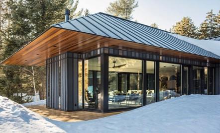 O casă de oaspeți construită pe structură metalică și înconjurată de pădurea din Vermont