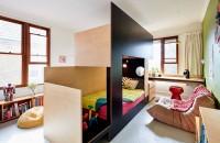 Un pat făcut pe comandă separă dormitorul comun si oferă spații pentru fiecare copil In loc sa creeze un pat supraetajat care sa stea sprijint de un perete, designerii au realizat un volum independent dintr-o combinatie de palacaje din lemn.