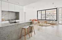 Un apartament amenajat cu granit gri și ziduri albe stălucitoare  Firma de arhitectura spaniola Raul Sanchez Architects a folosit, in reamenajarea unui apartament din Barcelona, materiale contrastante pentru a crea diferite zone in locuinta cu plan deschis.