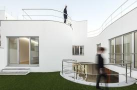 O casa cu forme rotunjite se strecoara printre volumele invecinate