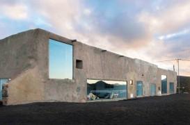 Casa din lut, calcar si sticla ce reflecta relieful vulcanic