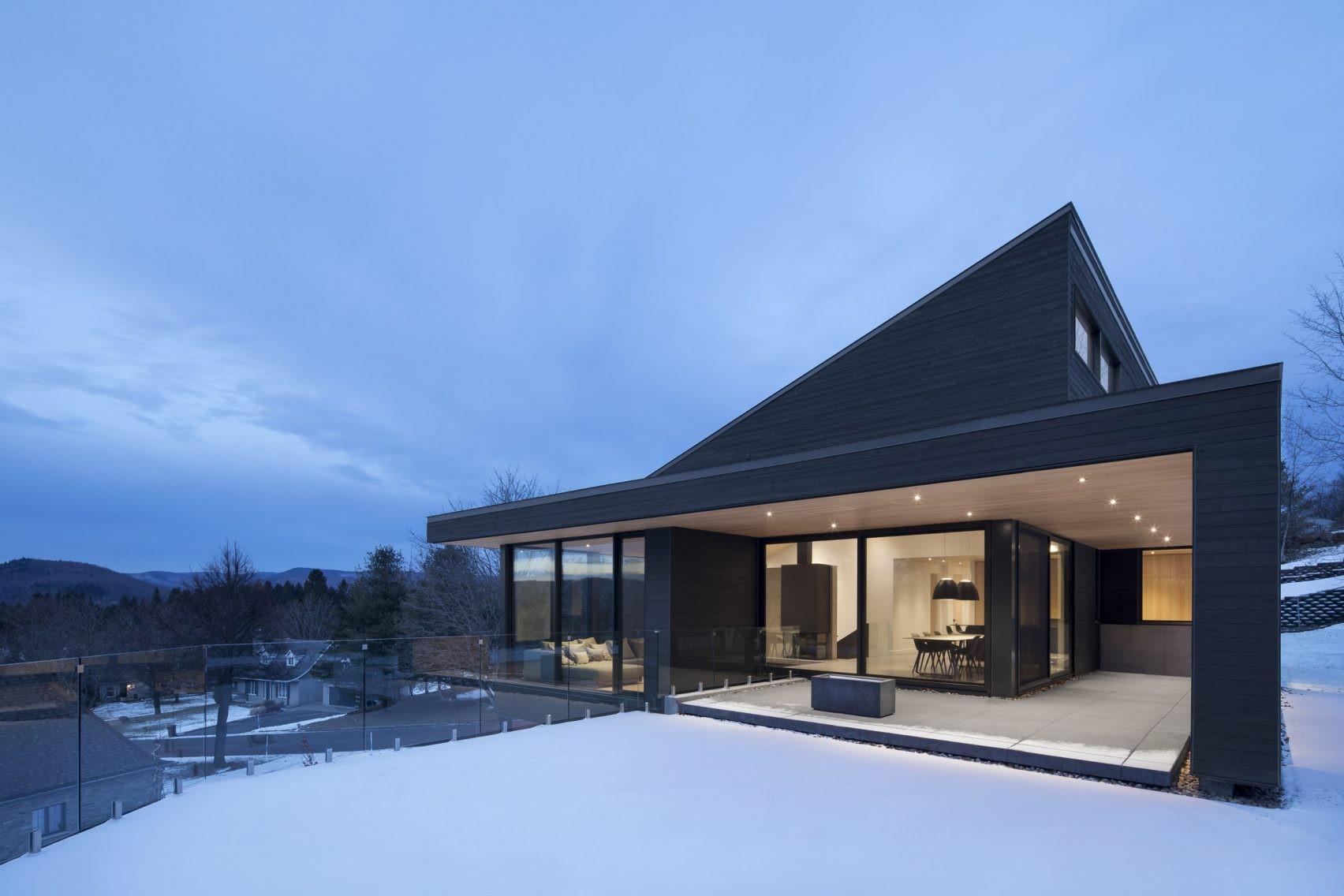 Casă cu volume din sticlă așezată pe panta unui deal înzăpezit din Quebec