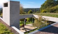 Un acoperis verde asigura continuitatea casei in peisajul inconjurator Luminatoare strapung din loc in loc acest