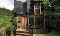 """Anvelopanta din sticla neagra pentru o casa dintr-o zona protejata """"Casa copac"""" este o creatie a"""