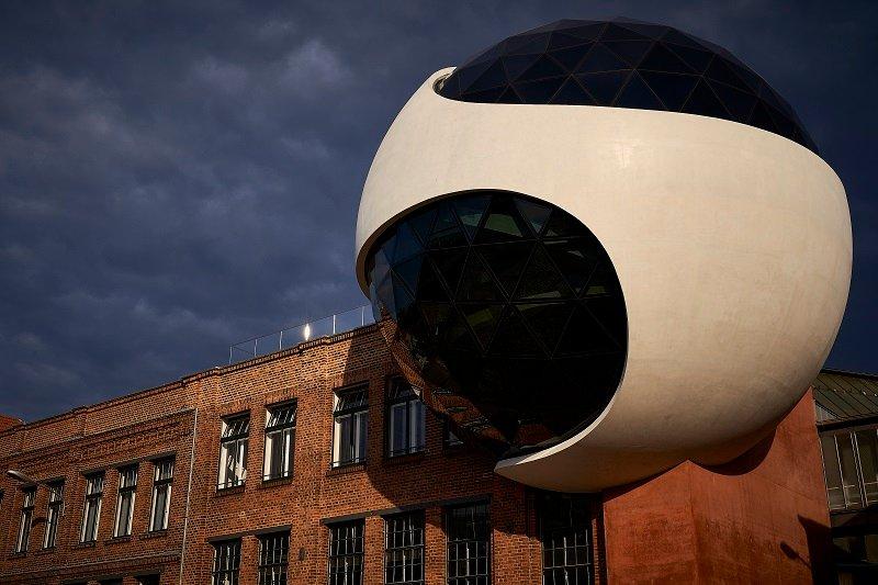 """O sferă din beton și sticlă, proiectată de Oscar Niemeyer, """"înfiptă"""" în colțul unei fabrici"""