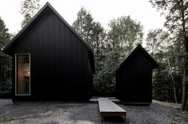 O casă neagră din metal se ascunde într-o pădure din Quebec