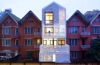 Casa insiruita, cu anvelopanta dantelata si gradini verticale O gradina verticala protejata de o anvelopanta dantelata invaluie partea din fata si cea din spate a unei case insiruite din Vietnam.