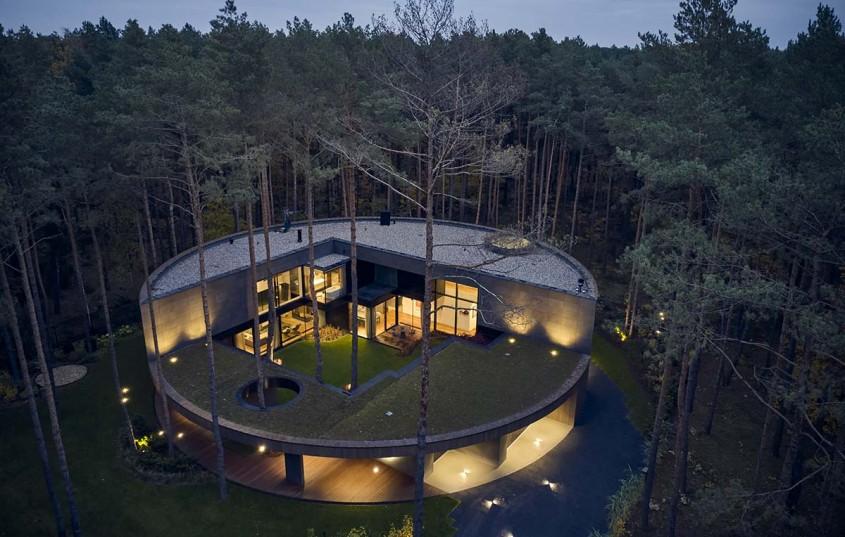O casă circulară construită printre arbori într-o pădure de pini