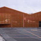 Bang Architect transforma fatada fabricii Calais Peanut cu ajutorul unui mesh portocaliu